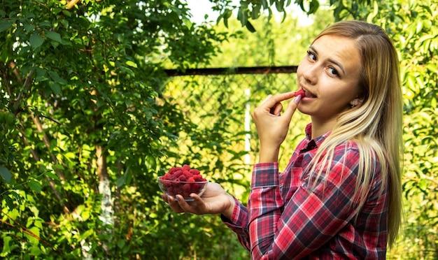 農場で熟したラズベリーの有機製品とボウルを保持している女の子。セレクティブフォーカス