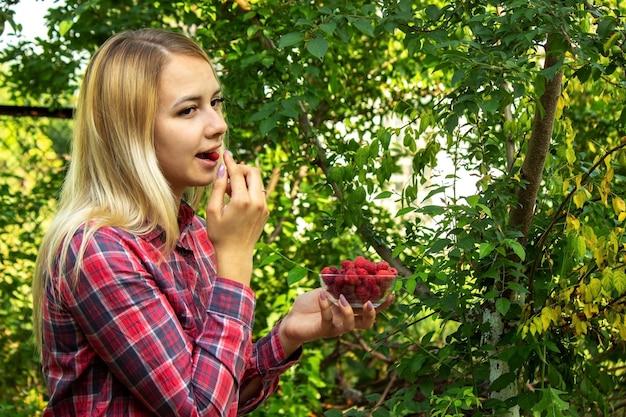 農場で熟したラズベリーの有機製品とボウルを保持している女の子。
