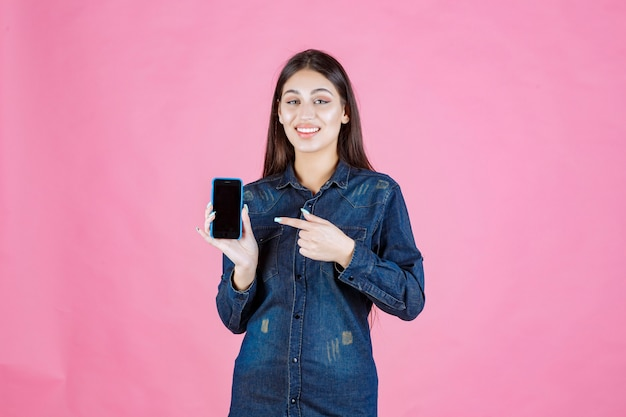 真新しいスマートフォンを持ってそれを指している女の子 無料写真