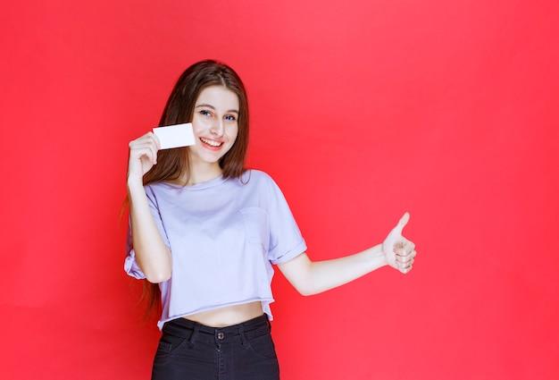 名刺を持って、肯定的な手のサインを示す女の子。