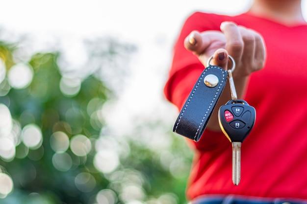 Девушка держит ключ от машины с дистанционным управлением.