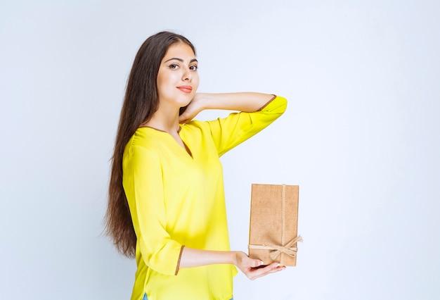 Девушка держит картонную подарочную коробку и чувствует себя позитивно.