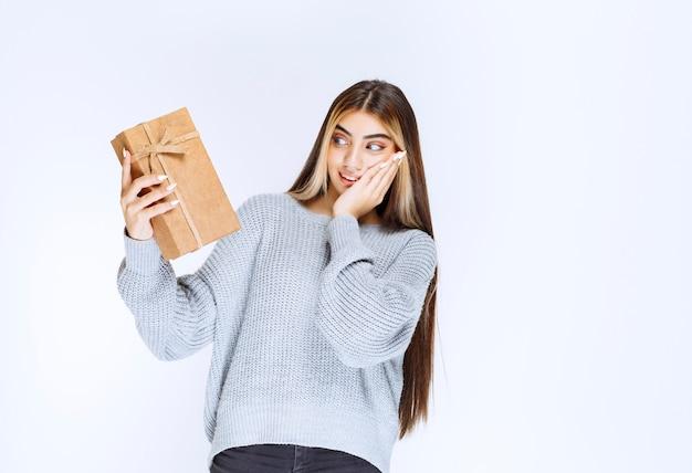 Девушка держит картонную подарочную коробку и выглядит удивленно.