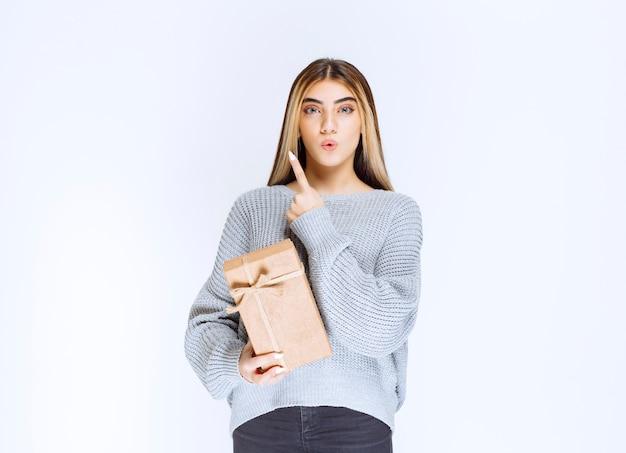 Девушка держит картонную подарочную коробку и указывая в сторону приемника.