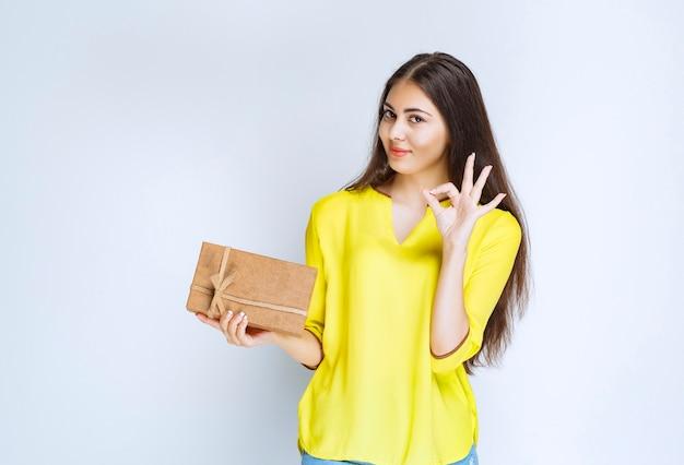 段ボールのギフトボックスを保持し、満足のサインを示す女の子。 Premium写真