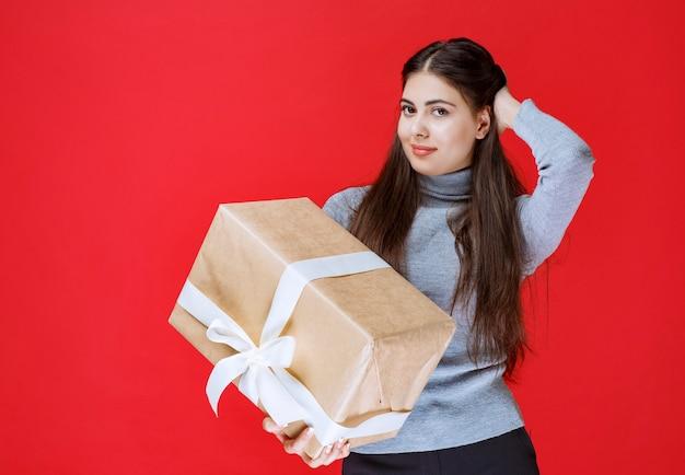 Девушка держит картонную подарочную коробку и думать.