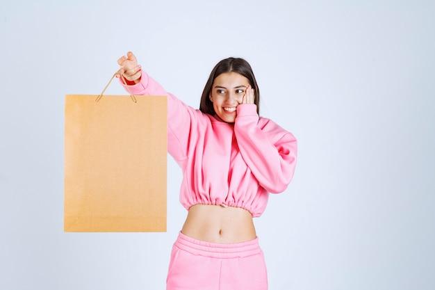 段ボールの買い物袋を持って興奮している女の子。