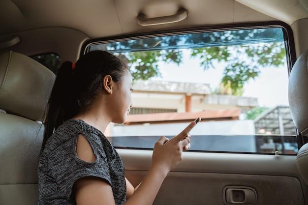 Девушка держит мобильный телефон, сидя в машине с открытым окном во время путешествия