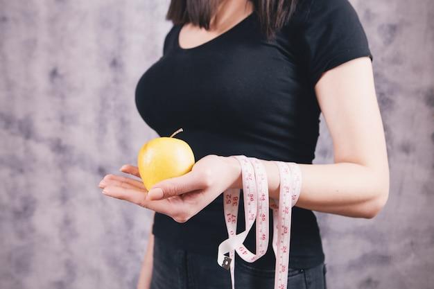センチメートルとリンゴを手に持った少女