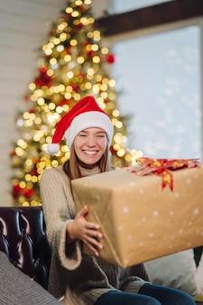 Девушка держит рождественский подарок в канун нового года. девушка смотрит в камеру