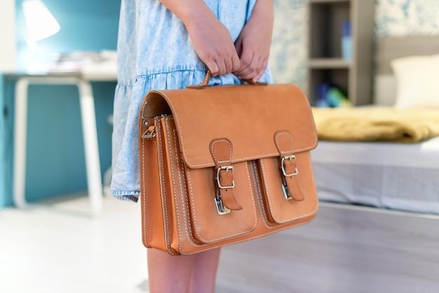 Девушка держит классическую кожаную школьную сумку в спальне крупным планом