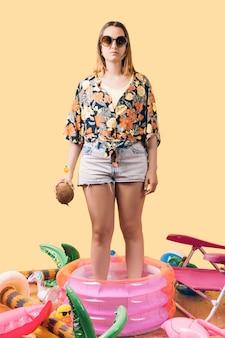 黄色の背景に膨らませて周りの小さなピンクのプールに立っているココナッツを保持している女の子