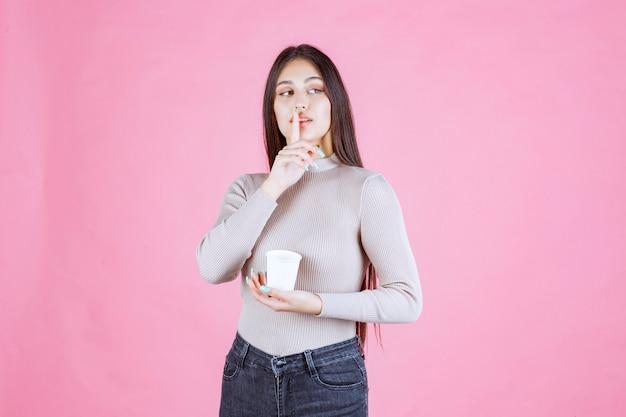 コーヒーカップを持って沈黙を求める少女