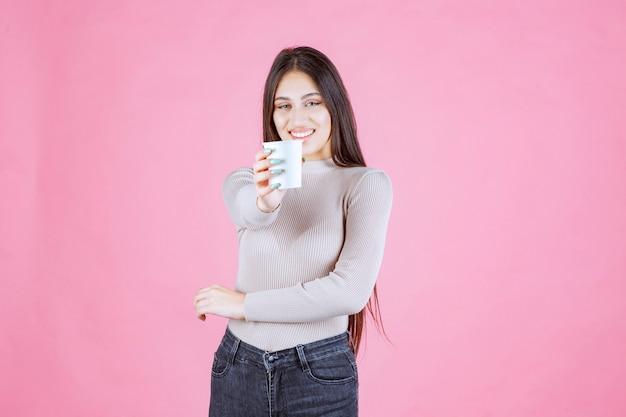コーヒーカップを持って、彼女のパートナーにそれを提供する女の子