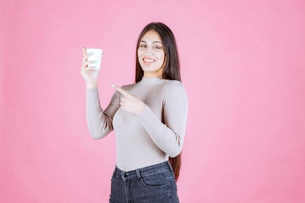 Девушка держит чашку кофе и указывает на нее