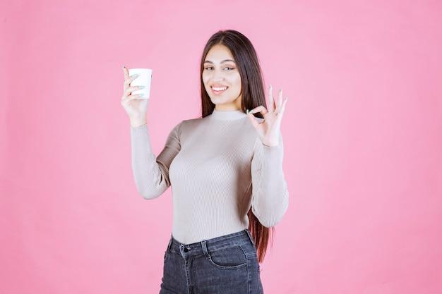 Девушка держит чашку кофе и указывает на хороший вкус
