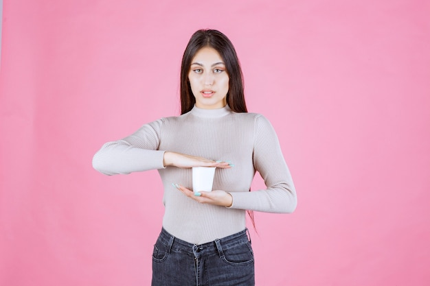 彼女の手の間でコーヒーカップを保持している女の子