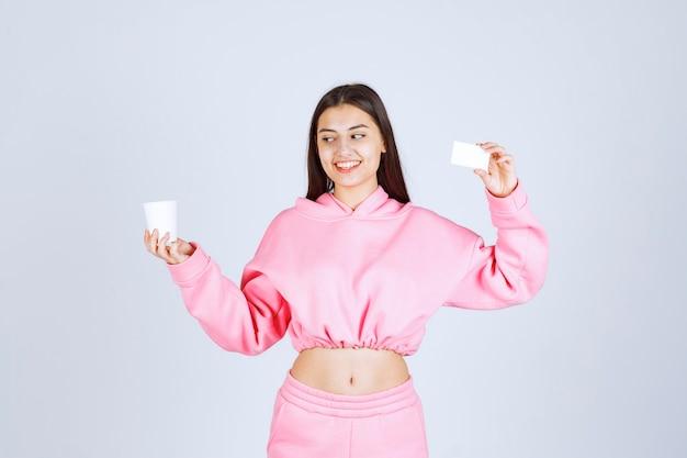 Девушка держит чашку кофе в одной руке и представляет свою визитку в другой руке