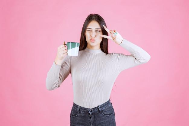 커피 잔을 들고 평화 메시지를 보내는 소녀