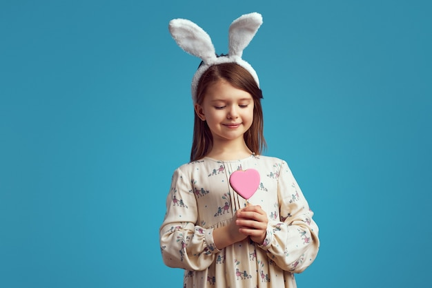 Девушка держит печенье в форме сердца в кроличьих ушах над синей стеной