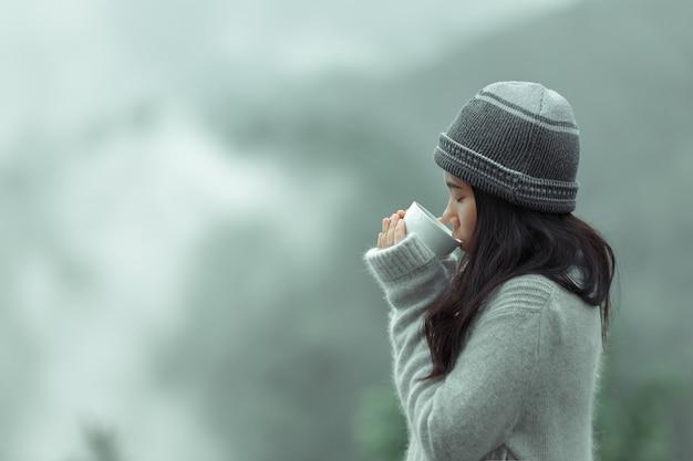 Девушка держит чашку кофе на холодном ветру