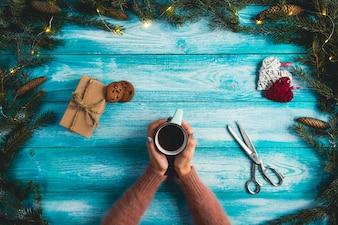 木製の青い背景にホットココアのカップを持っている少女。クリスマスのコンセプト。