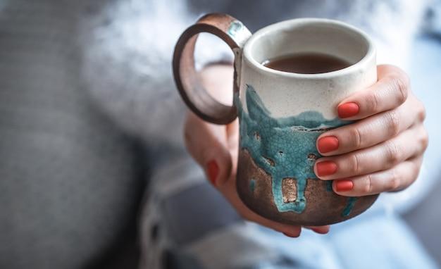手でお茶のカップを保持している女の子