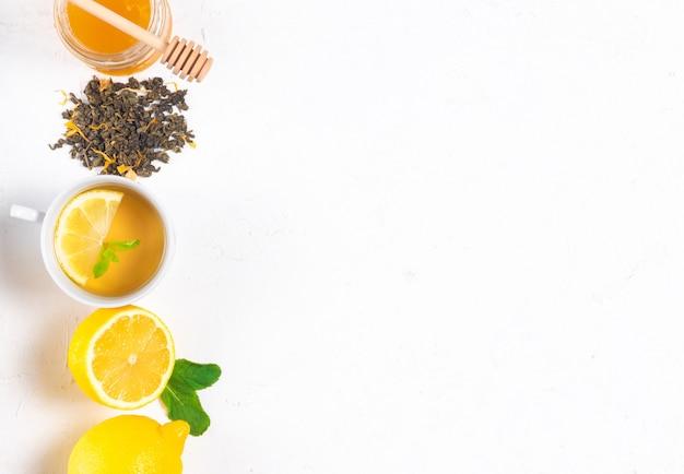 Девушка держит чашку чая с лимоном и медом