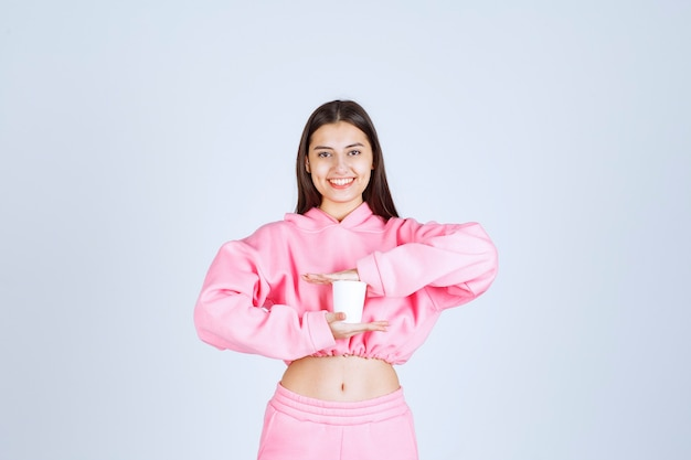 Девушка держит одноразовую кофейную чашку обеими руками