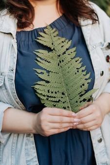그녀의 손에 고 사리 잎을 들고 소녀 봄 자연 녹색 식물입니다. 봄 프리미엄 사진