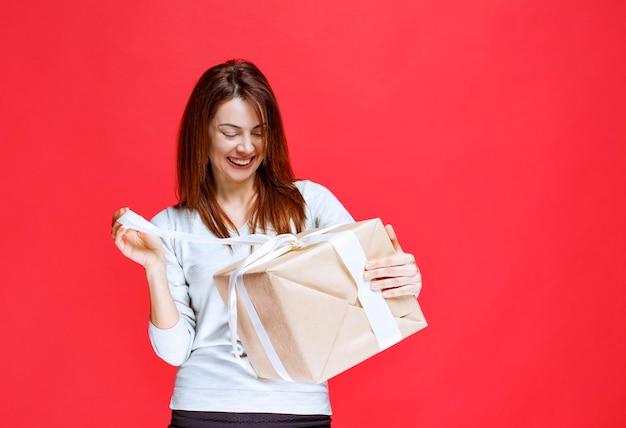 Девушка держит подарочную коробку и открывает ее.