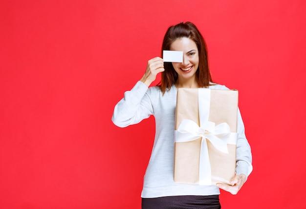 Девушка держит подарочную коробку и представляет свою визитную карточку.