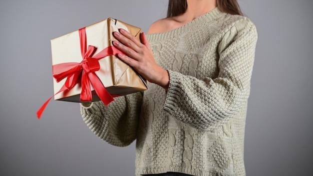 Девушка держит подарок в вязаном свитере.