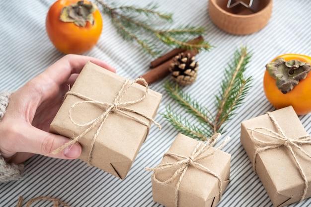 그녀의 자신의 손으로 포장 선물을 들고 소녀 클로즈업. 크리스마스 장식, 천연 소재로 만든 크리스마스 선물 상자 디자인. 새해 분위기, 크리스마스 준비.