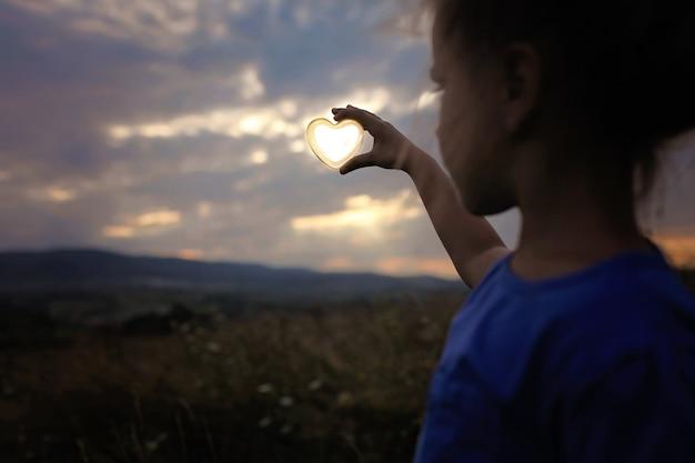 曇りの夕暮れの空、愛とエコロジーの概念、抽象的な背景の上に太陽とガラスの心を保持している女の子