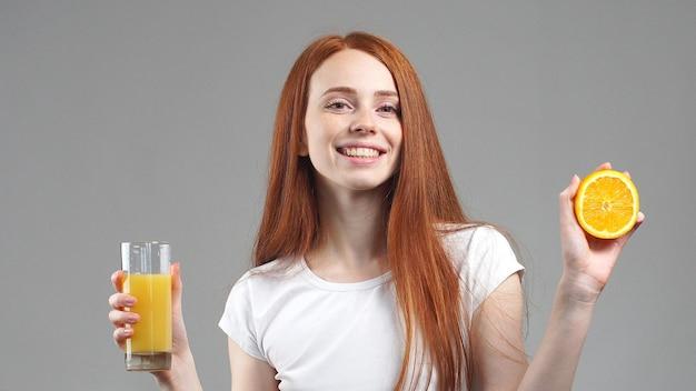 オレンジジュースとオレンジのグラスを持っている女の子