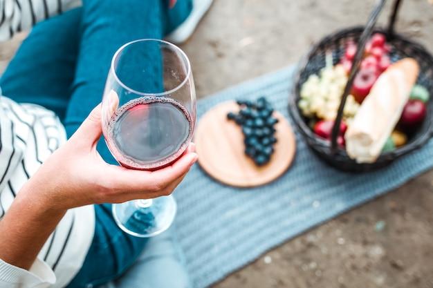 彼女の手に赤ワインのグラスを持っている女の子