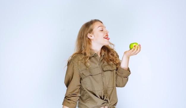 Девушка держит зеленое яблоко в ладони.