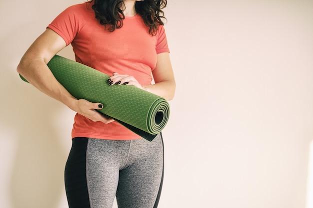 Девушка держит в руках зеленый коврик для фитнеса - женщина, использующая зеленый коврик для йоги - девушка на тренировке в концепции здорового образа жизни спортивный коврик