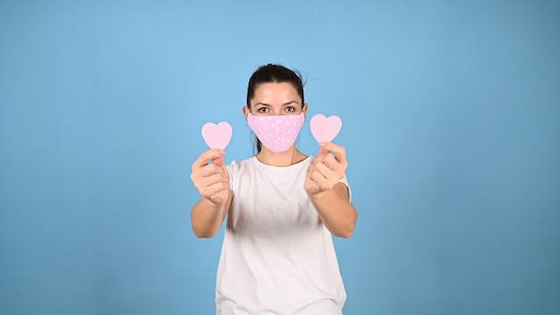 Девушка держит сердце руками в маске. фото высокого качества