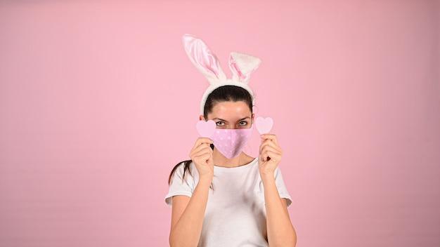 Девушка держит сердце руками в маске на розовом фоне. фото высокого качества