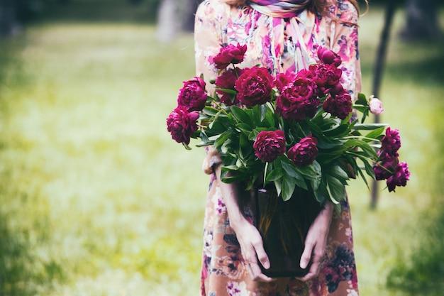 牡丹の花束と瓶を保持している女の子