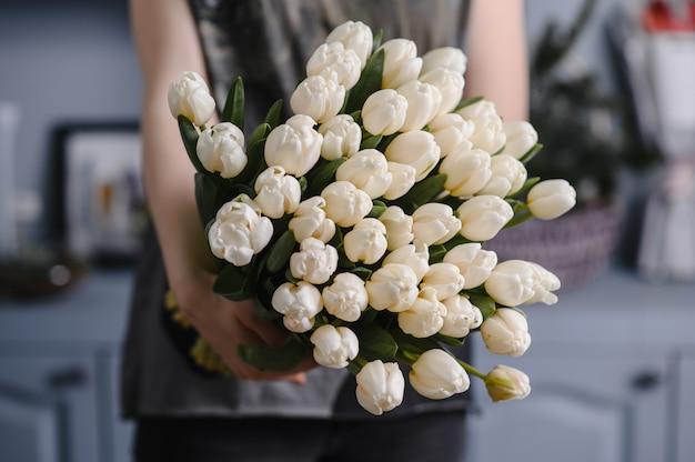 Девушка держит в руках большой букет тюльпанов
