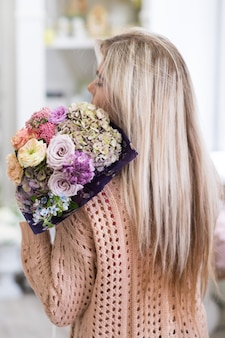 さまざまな花の壮大な花束を持っている女の子。美しい花の構成。ロマンチックな日付の概念