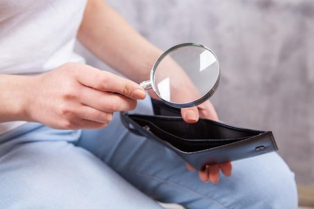 Девушка держит увеличительное стекло и бумажник
