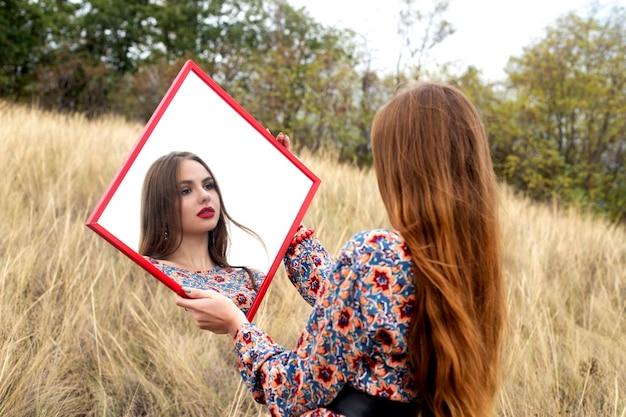 Девушка держит зеркало со своим отражением