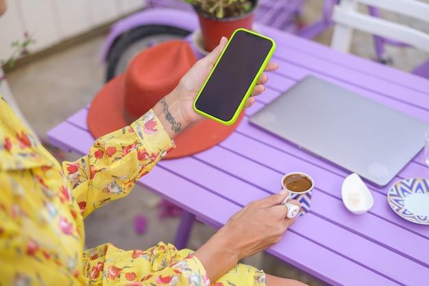 카페에서 빈 검은색 화면이 있는 휴대전화를 들고 있는 소녀, 노트북, 터키식 커피가 탁자 위에 있습니다