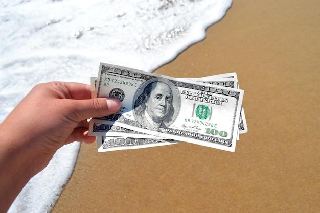 Девушка держит банкноту в 300 долларов на фоне морских волн
