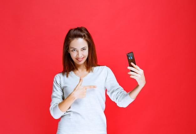 新しいモデルの黒いスマートフォンを持って、前向きで満足している女の子。