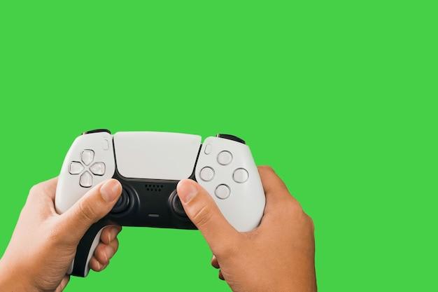 녹색 배경에 고립 된 차세대 흰색 게임 컨트롤러를 들고 소녀. 크로마 키.